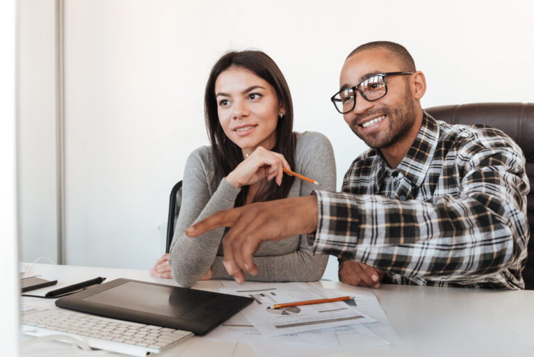 Picture of young concentrated business couple using computer in office. Look at computer.