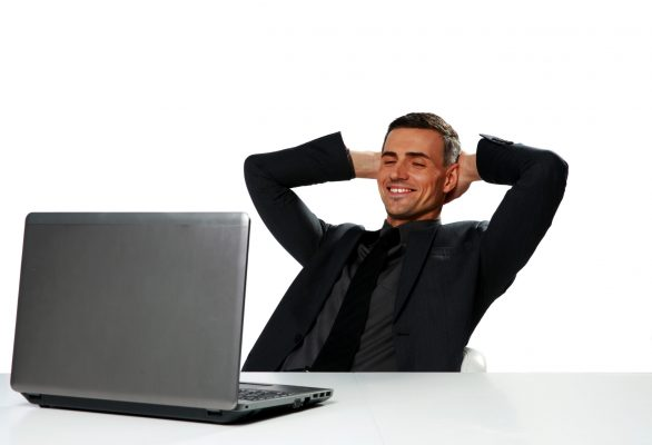 Relaxed happy businessman sitting at the table with laptop isolated on a white background